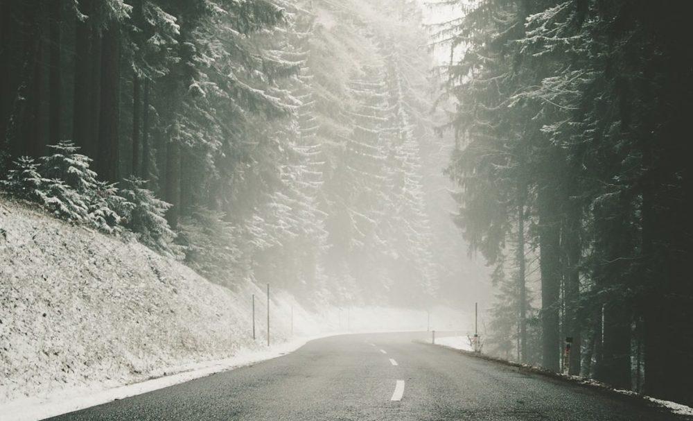 Durch S-Pro EisWeg befreite Straße durch den Wald im Winter.