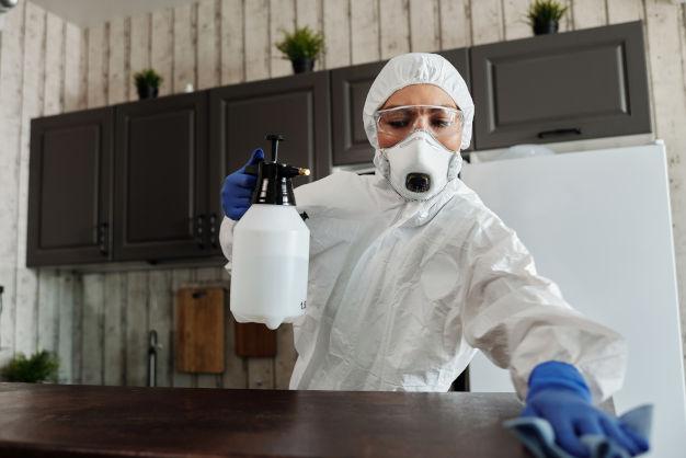 Frau mit Schutzkleidung und Gasmaske putzt ihre Ablage
