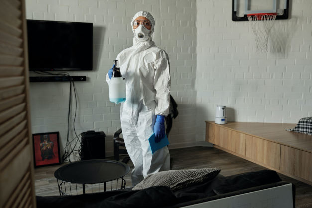 Frau mit Schutzkleidung und Gasmaske steht in ihrem Wohnzimmer